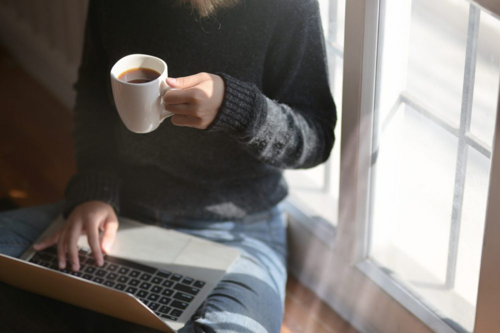 Close-up view of young freelancer working on her project and drinking hot cocoa while sitting near the windows at her workplace
